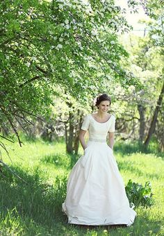 Custom scoop neck modest blush pink wedding dress from Anne Barge with short sleeves and pleated detail on the bodice and scoop pockets in the ball-gown skirt