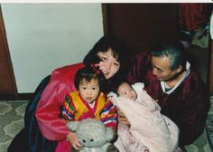 When I was young. With mom and grandfather and baby cousin. I am holding a sheep doll with mom. Grandfather holds and stares at baby cousin.