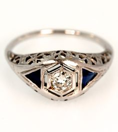 Circa 1930, this engagement ring features a 0.22 carat VS2 G Old European cut diamond flanked by two Trillion cut synthetic Sapphires. Crafted in 18k white gold, the sided show off an intricate filigr