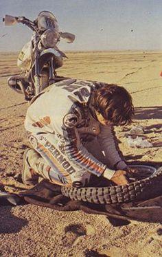 Hubert #Auriol ripara il pneumatico della sua #BMW durante la #Dakar 1982.