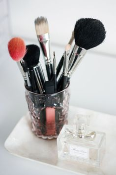 Fill a vintage perfume bottle with makeup cleaner in a decorative try along with your makeup brushes.  Now you can simply spray the brushes, give them a wipe and sit them back in the jar to dry until you use them the next day.
