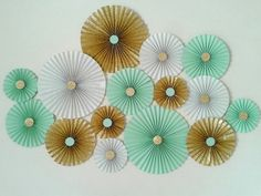PERFECT ADDITIONS TO ANY CELEBRATIONS ! Hot , trendy and fun decorating style for a backdrop or Photo-prop! These fans would make a lovely backdrop to a party table for a Mint and Gold Bridal shower, birthday, cake smash photography, baby shower or wedding celebrations. This is a set of 15 MINT, WHITE & GOLD Paper rosettes consisting of .♥ LARGE - 12 inches - 3 nos. ♥ MEDIUM - 8.5 inches - 7 nos. ♥ SMALL - 6 inches - 5 nos. Made from Mint, White & minimal shed glitter gold paper. The ce...