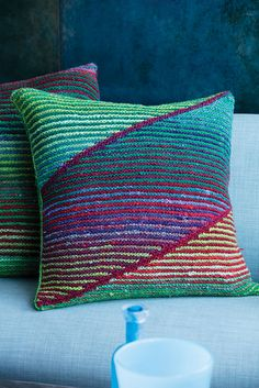 Simple yet striking in two-row garter stripes, this pillow alternates skeins of Kureopatora to create coordinated contrast among the saturated green, lime, red and violet shades of colorway #1019. At the front, short rows form slanted panels that are divided by four-row bands; at the back, the stripes are horizontal. The pieces are seamed in finishing.