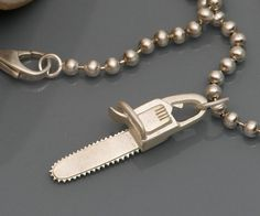 Looking for a cute way to show off your inner pyscho? Then you should try the chainsaw necklace charm - this unique hand made silver necklace charm is a great gift idea for people who love unusual and interesting jewelry and comes with the necklace chain too.