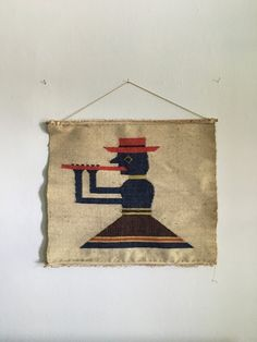 small abstract weaving of a figure i believe is playing the flute! though this seems to be in the style of a peruvian tapestry, the weaving was