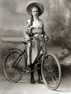 A vintage bike and a lovely young lady, with a long braid of hair, wearing a wide-brimmed hat.