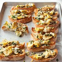 Artichoke Bruschetta 2 14 ounce cans  artichoke hearts, halved 1/2 cup chopped parsley 8 cloves garlic, chopped 1/4 cup EVOO 2/3 cup dry white wine 8 slices  ciabatta, toasted 1/2 cup grated parmesan