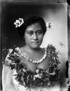 By: Andrew, Thomas Date: circa 1910  Description: An unidentified Samoan woman wearing traditional dress and frangipani flowers in her hair. She is wearing a ceremonial headdress (tuiga), and holding a wooden nifooti (cane knife).