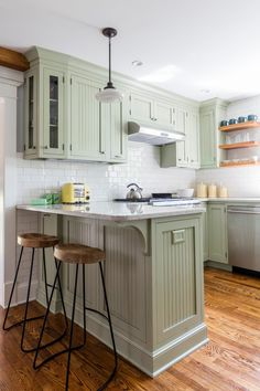 Light green cabinets pair with wood floors in a craftsman style kitchen