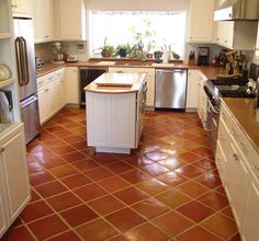 Traditional Saltillo Terra Cotta floor tile in a beautiful white, country kitchen. I love the pop of warm hues.