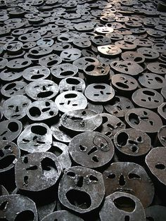 Shalechet - Fallen Leaves by Menashe Kadishman @ Jewish Museum, Berlin  Over 10,000 open-mouthed faces coarsely cut from heavy, circular iron plates cover the floor. A powerful reminder of the death and suffering.