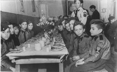 Young boys dressed in Betar Zionist youth uniforms, are about to eat a meal in the dining room.