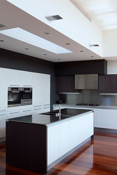 The rich, dark framing cabinetry provides a modern contrast to the central white cabinets and ceiling detail. Stainless steel back splash