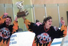 Right, Taos Ice Tigers River Chalker, left, and Nate Sechrist, right, skate a victory lap with the state championship trophy after their 3-1 win against Los Alamos on March 8. Photo by Elliott Martin
