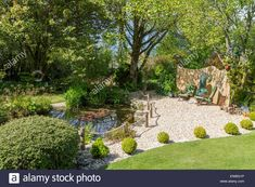 Marvelous English garden with pond area and gravel seating area Stock Photo