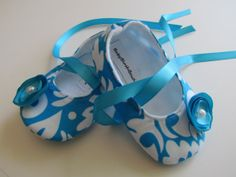 Blue Scroll Baby Soft Ballerina Slippers. It has a Turquoise flower embellishment. This shoes are soft for those delicate baby or infant feet. The ribbon tie are long enough to wrap/tie around the ankle. #timelesstreasure