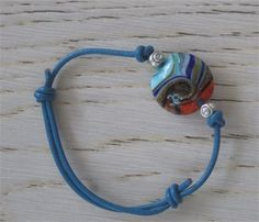 Beautiful Italian glass bead with lively colors, blue leather cord and adjustable clasp. Wear it alone with the Silk orange macrame bracelet as shown in the picture or with anything that you have and look S T U N N I N G!!! Measurements: Fits all wrist sizes. Its adjustable   I really enjoyed making it, hope youll enjoy wearing it.   From my heart to yours,   Mahsan