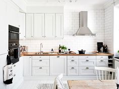 White kitchen with butcher block counter tops and subway tile
