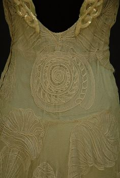 "WORTH NET EVENING GOWN with SEASHELL DESIGN, c. 1932. Back Detail. Sleeveless pale seafoam green V-neck decorated with large shells of various types, the straps with iridescent sequin decoration and scattered rhinestones at shoulder and down low back, attached seafoam crepe de chine slip, side closure. Label ""Worth""."