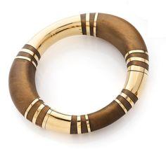 RENE BOIVIN  Bracelet rigide ouvrant formé d'un jonc elliptique en bois de santal coupé de segments et d'anneaux en or jaune, l'un pivotant.  Travail de la Maison Boivin.  Vers 1970.
