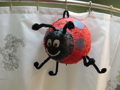 Ladybug Pinata!  Use 4 layers of paper mache over two balloons (one large and one small secured with duct tape).  For the fringe, fold crepe paper in half long ways and cut 3/4 of the way through leaving the folded edge in tact.  Glue in rounds around structure.  Cut three sides of a square in the top and fold back to access inside.  Add legs and antenas by poking holes and taping pipe cleaners down inside..add large pom poms to ends.  Use construction paper for spots and eyes.