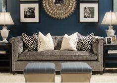 glamorous living room with grey velvet sofa, metallic sunburst mirror and navy blue walls
