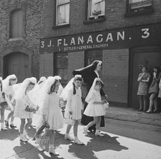 A young nun walking Holy Communion girls past no. 3, Halston Street, Dublin on the feast of Corpus Christi.   Date: 5 June 1969. Photo via National Library of Ireland.