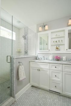 Gray marble diamond pattern shower accent tiles trim a walk-in shower enclosed with a glass door.