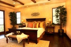Warm yellows in the walls, bedding and floor coverings contrast with the rich dark hardwood floors and furniture.