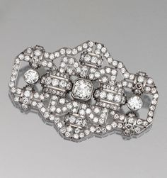 ART DECO DIAMOND BROOCH & RING, 1930s.  The brooch of openwork geometric design, set throughout with circular-cut diamonds, accompanied by a ring bezel-set to the centre with a similarly-cut stone,  all mounted in platinum.  The central diamond on the brooch & the diamond on the ring can both be detached & set on accompanied ring fitting. Further accompanied by a black cord & its diamond-set hook allowing the brooch to be worn as a pendant.