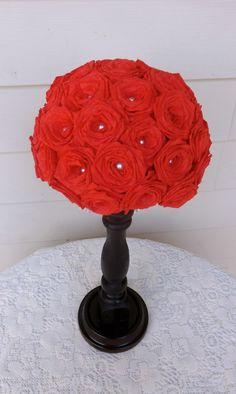 Red paper rose and pearl centerpiece on a black stand! Gorgeous addition to a black white and red wedding.
