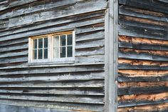 Corner Detail of Weathered Barn Walls with Two Windows and Rustic Gray and Brown…
