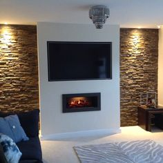 A false chimney breast, Split slate in the alcoves with mood downlights. A fantastic electric inset fire with full remote control.