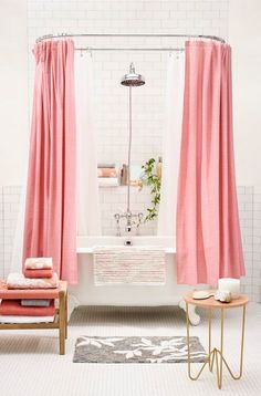 Soak in suds in this feminine pink bathroom that features a pink curtained bathtub w/ porcelain white tiles, stainless steel shower head, & matching pink & white towels.