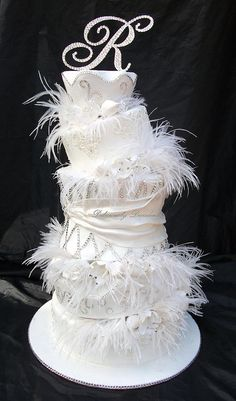 """Bling wonky tonk cake...    5""""7""""8"""" double 9""""10""""   display for a magazine photoshoot  this is my ode to sex in the city hehe the shoot is an all white one  bek from crystal couture blinged the cake and did the topper, angled sections are stuffed with white gumpaste tulips, scruch roses, crystal flowers and ostrich feathers"""