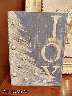 "Artsy VaVa: ""JOY"" Wood Blocks.  She painted a base coat of white acrylic paint. When dry apply vinyl letters that she cut out with a Cricut to spell  JOY.  Then painted over the entire block with blue acrylic paint. Using the same white paint as the base coat, she painted a simple tree & peeled off the vinyl letters,  gave the block a good sanding & added buttons for ornaments."