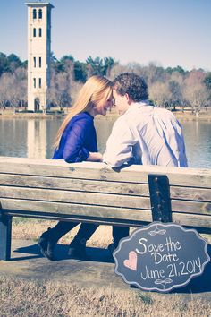 save the date photo idea- couple sitting on a bench staring at each other and in front of the bench is a sign that says the date