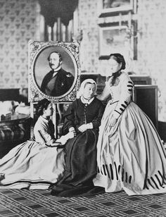 Queen Victoria and two daughters in mourning, October 1863. Left to right: Princess Louise, the Queen, and Princess Alice. Prince Albert is depicted in a painting behind them, almost two years after his death. Photo taken at Balmoral. From the Royal...