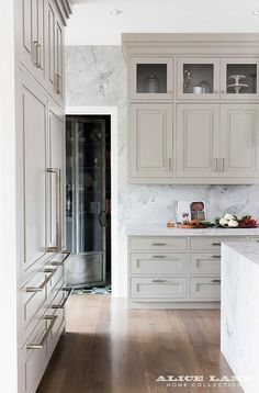 Coastal Contemporary kitchen with super white granite countertops, walls and island. Photo by Nicole Gerulat Kitchen Cabinet Handles, Grey Kitchen Cabinets, Kitchen Cabinet Colors, Upper Cabinets, Kitchen Island, Tall Cabinets, Kitchen Counters, White Cabinets, Cabinet Hardware