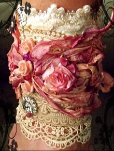 A cuff with dyed and crinkled Rayon seam binding, vintage lace and dyed cabbage roses.