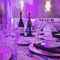 Table Numbers in front of table wines for a masquerade themed wedding reception with stunning purple uplighting and specialty iridescent linens throughout!