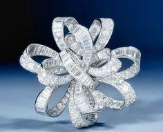 VAN CLEEF & ARPELS  An impressive Art Deco diamond 'flot de rubans' bow brooch,  designed as an openwork bow of intertwined baguette and circular-cut diamond ribbons, mounted in platinum.  Paris, circa 1937.