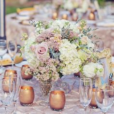 Vintage glass vases filled with hydrangeas and roses were surrounded by small votives for added romance.