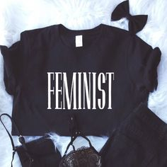 "Feminist Tshirt in Black - S, M, L This feminist shirt in black is a great way to show your support for feminism. This shirt displays a large bold ""feminist"" graphic across the front chest.   To purchase: Please comment what size you'd like and I will create a custom listing for you to purchase.    Item is 100% NEW   Available Sizes: S, M, L  Interested in multiple items? Ask for a 10% bundle discount. Tops"