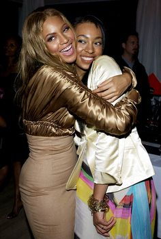 Beyoncé Knowles in a brown cropped jacket and dress // Solange Knowles in a cream satin jacket and printed skirt