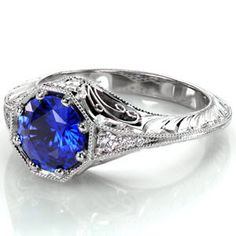 Design 2855 - Design 2855 is a stunning example of elegance with a rich blue hue of the 1.25 carat round cut sapphire taking center attention. Crafted in 14k white gold, single wheat hand engraving and graduating round cut diamonds adorn the knife edge band. Surprise stones and hand formed filigree curls accentuate a vintage look.