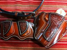 Tooled leather pancake holster with matching dual-magazine pouch and gun belt.