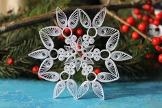 This 4 (10cm) white paper quilled snowflake ornament is elegant and perfect for hanging on a Christmas tree, making a garland, framing it, or