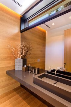 In this modern bathroom, there's hidden lighting in the ceiling that creates a warm glow on the wood wall and floor.