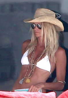 Elle Macpherson wearing an armband + wooden beads/metallic beads necklace